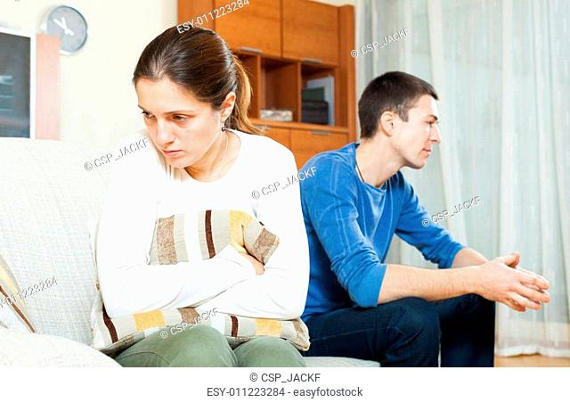 Family conflict. Sadness woman against unhappy man
