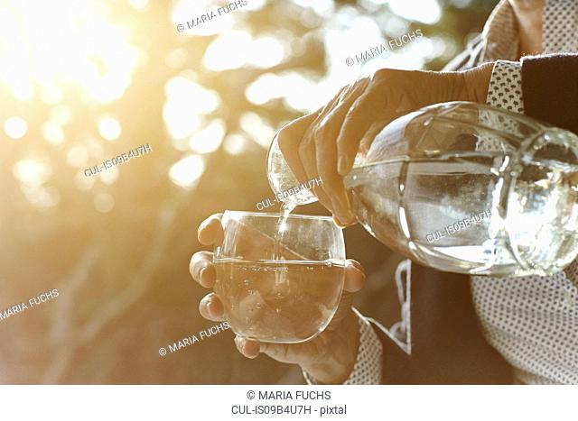 Hands of senior woman pouring glass of water by window