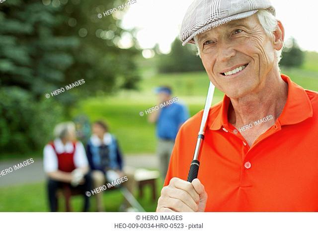 portrait of senior golfer with club on tee-box