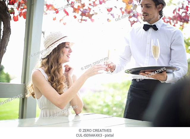 Waiter serving champagne to young woman in garden restaurant