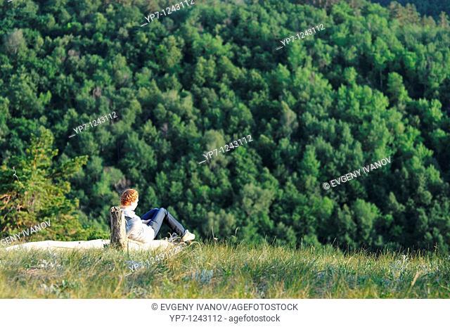 Girl sitting on a high hill near the steep in Russian National Park 'Samara Luka'
