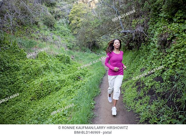 African American woman running on forest path