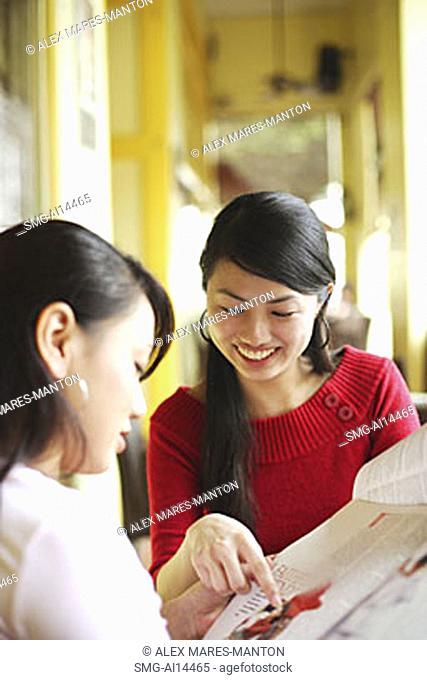 Young women in cafe, looking at newspaper
