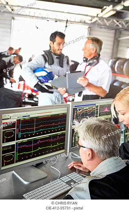 Formula one team reviewing diagnostics in repair garage