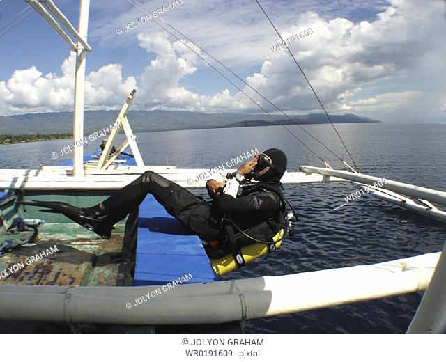 Diver making a back roll of a local dive boat called a 'Banca' Moalboal philippines