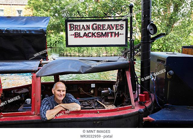 Blacksmith sitting on his working narrowboat on a waterway, looking at camera, smiling