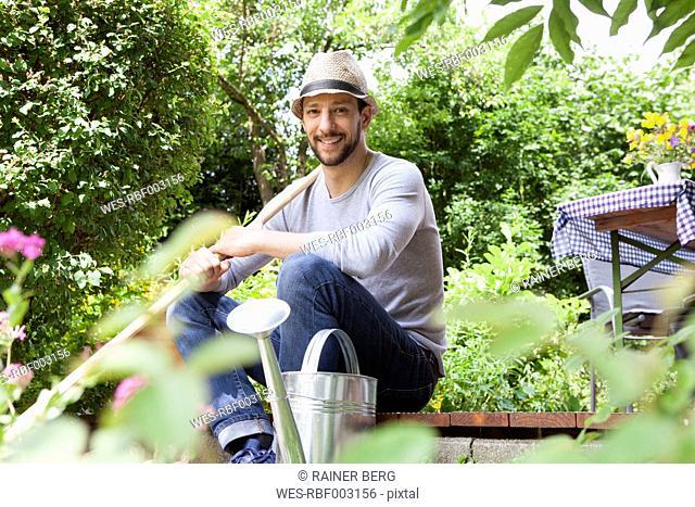 Smiling man sitting on garden terrace
