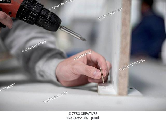 Close up of carpenter's hand using hand drill in wood workshop