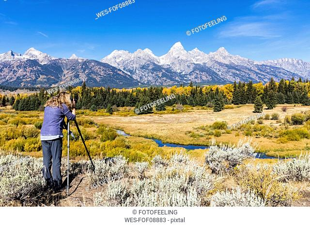 USA, Wyoming, Rocky Mountains, Grand Teton National Park, Snake River, Cathedral Group, woman taking picture of Teton Range