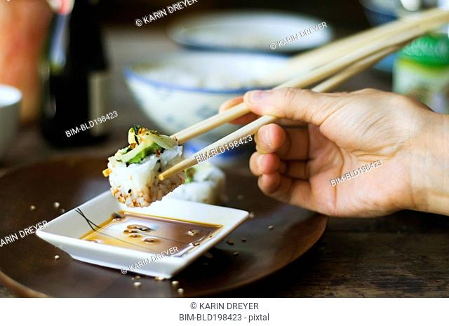 Person eating sushi with chopsticks