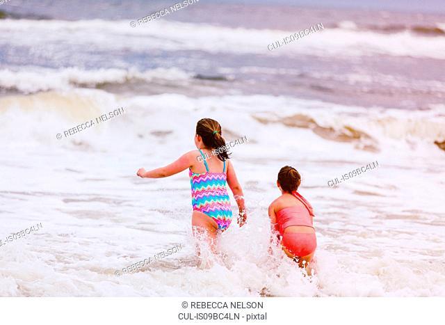 Two girls playing in ocean waves, rear view, Dauphin Island, Alabama, USA