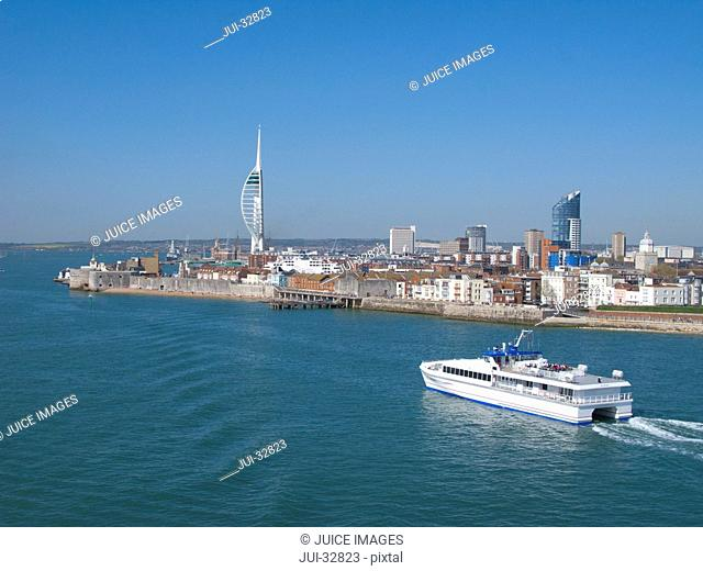 Ferry boating past cityscape of Portsmouth with modern spire in background