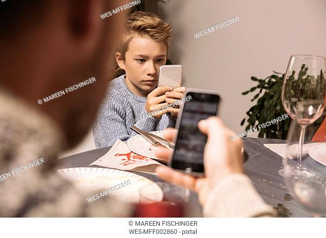 Boy playing with his smartphone after Christmas dinner