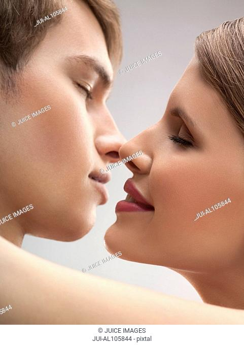 Close-up of young couple about to kiss, studio shot