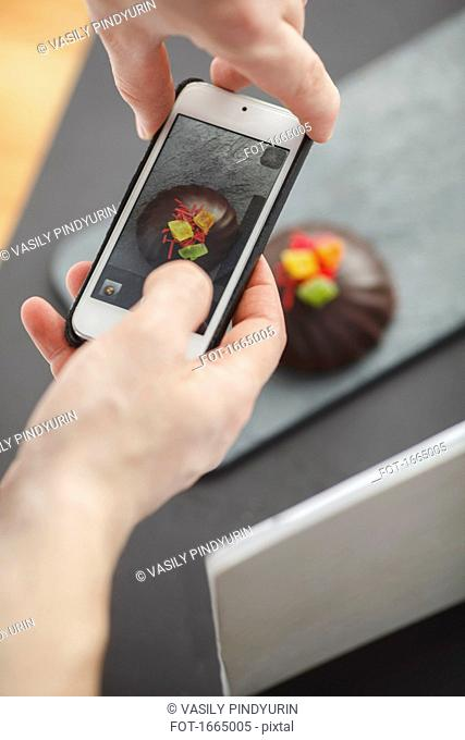 Cropped image of man photographing dessert on table through mobile phone