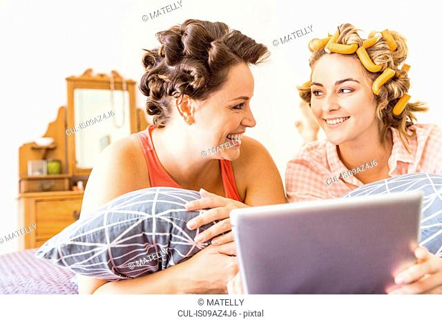 Two female friends, foam rollers in hair, lying on bed, using digital tablet