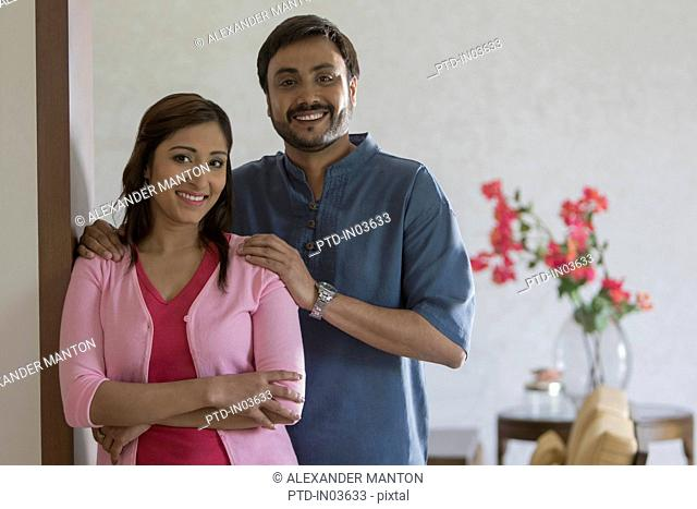 Woman and man arms folded looking at camera smiling