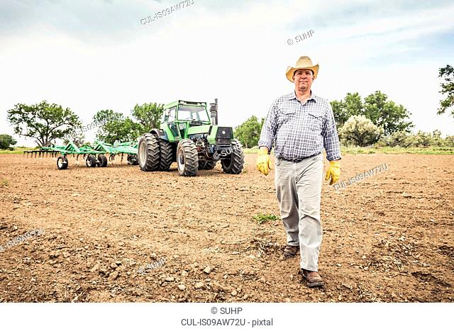 Farmer walking from tractor and plough in field