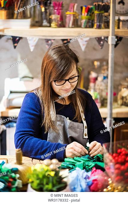 Woman working at a table in a craft workshop, making a paper flower wreath