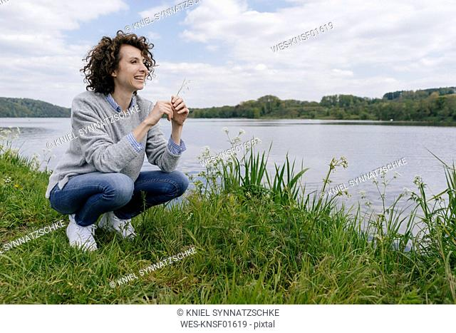 Woman crouching at lakeshore, smelling grass blade
