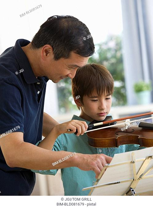 Father teaching son to play violin