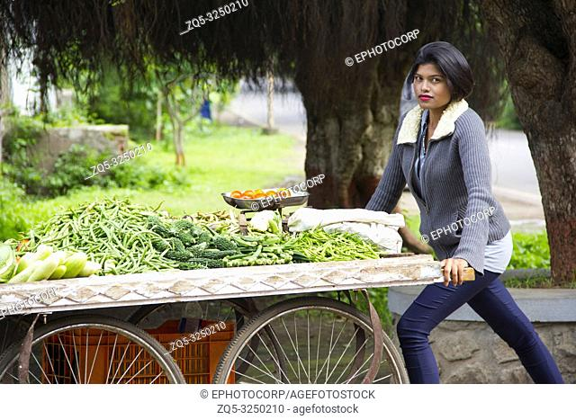 Young Indian girl with short hair selling vegetables on a cart, Pune