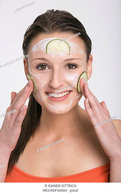 Young woman applying a cucumber face mask