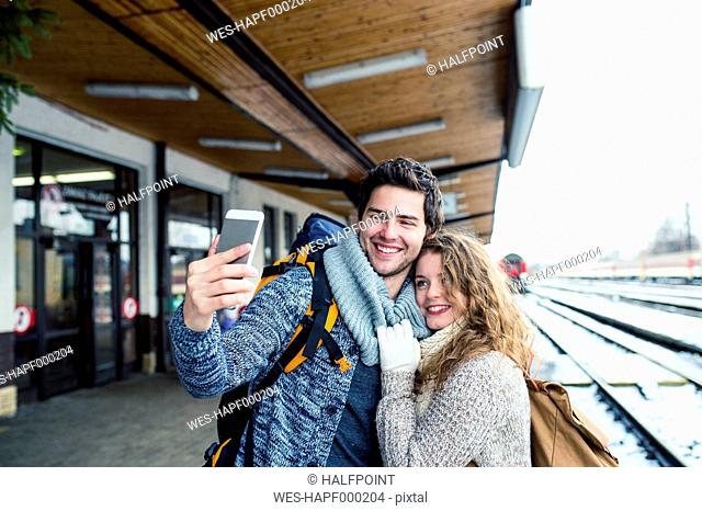 Happy young couple on station platform taking a selfie