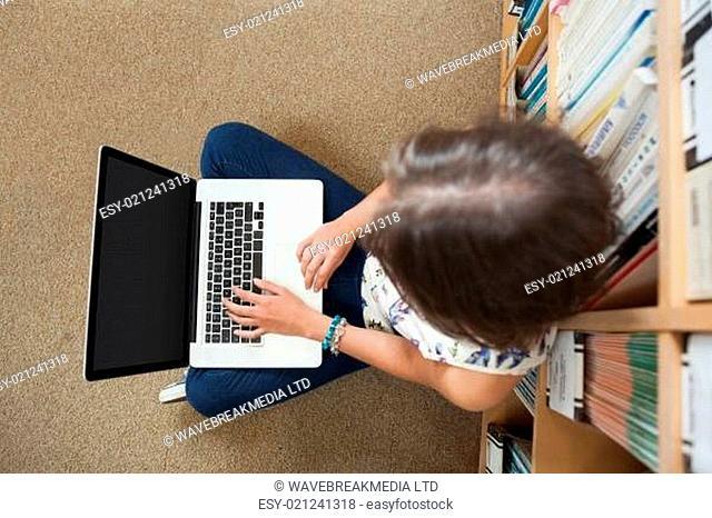Student against bookshelf using laptop on the library floor