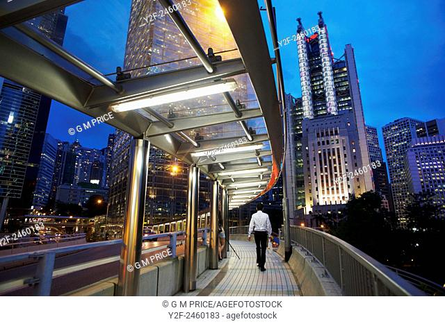 man on pedestrian walkway with Hong Kong Admiralty district skyline at dusk