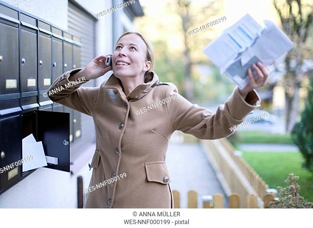 Happy woman telephoning with smartphone holding letter in her hand