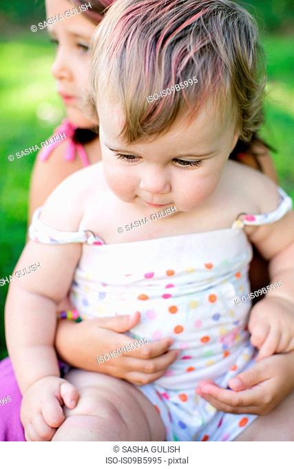 Close up of female toddler sitting on girl's knee in garden