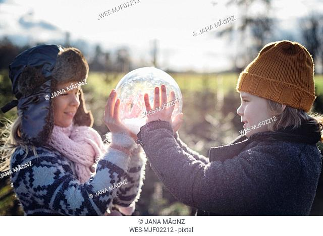 Brother and sister looking into crystal ball filled with snow, making a wish