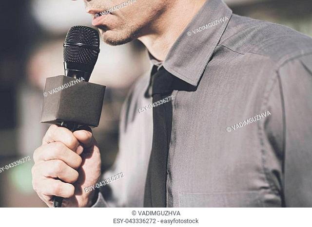 TV reporter at work. The man speaks into the microphone, he is dressed in a gray shirt and black tie
