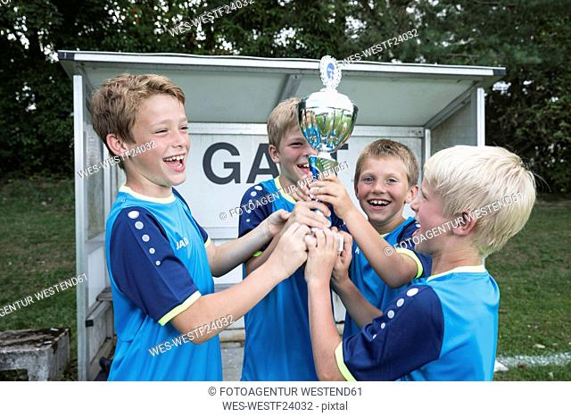 Young football players cheering with cup