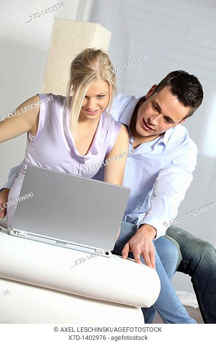couple sitting in front of laptop shopping in internet