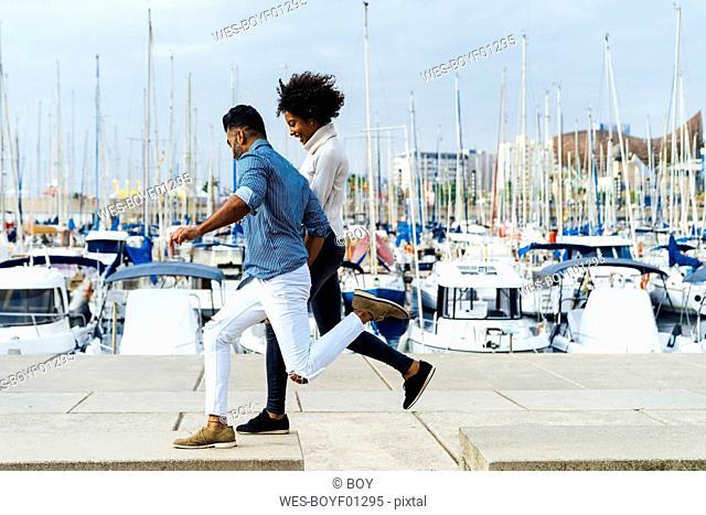 Spain, Barcelona, happy couple having fun at the marina