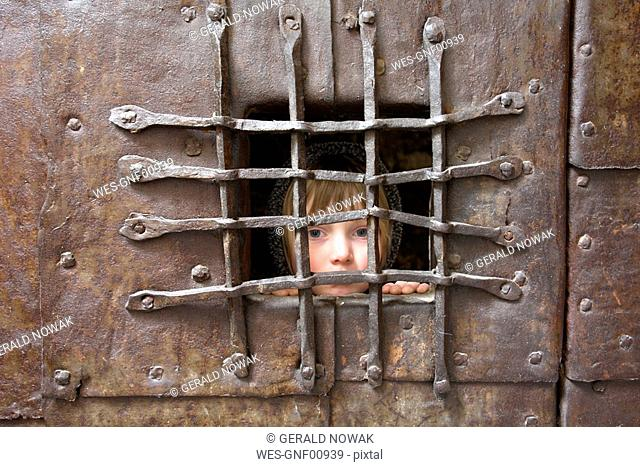 Italy, South Tyrol, Potrait of a girl behind bars