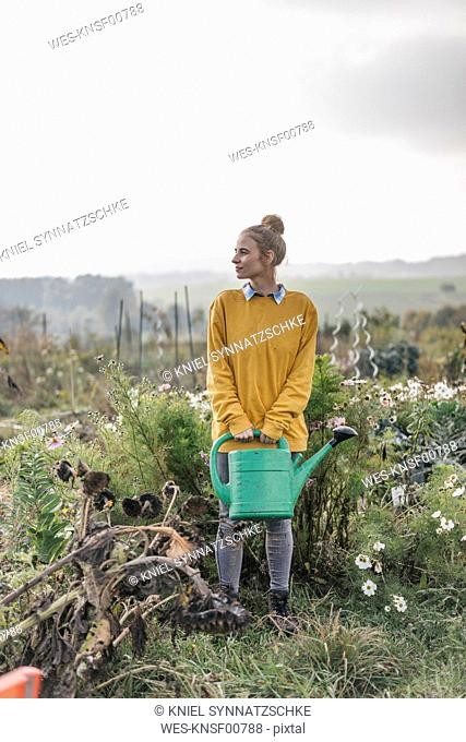 Young woman holding watering can in cottage garden