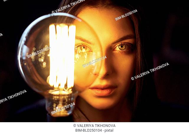Face of Caucasian woman illuminated by energy efficient light bulb