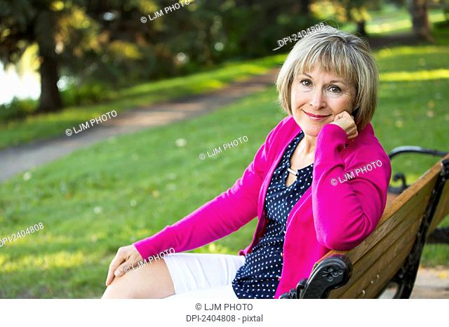 Portrait of a mature woman sitting on a park bench; Edmonton, Alberta, Canada