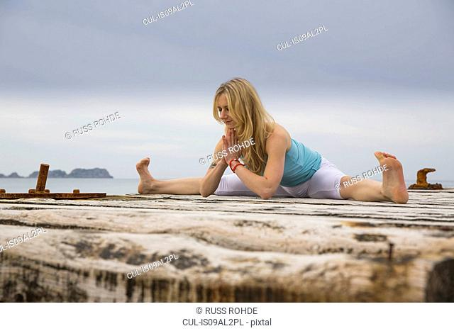 Mid adult woman with hands together practicing yoga on wooden sea pier