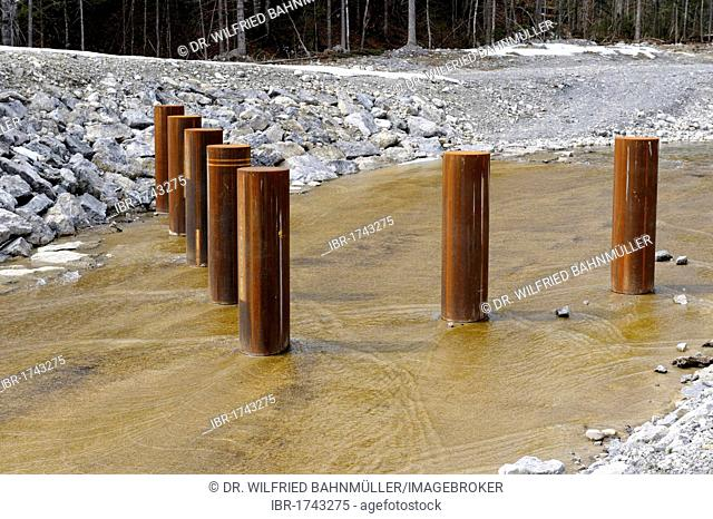 Flood protection, flood control beams in a stream bed to guard against flowing debris