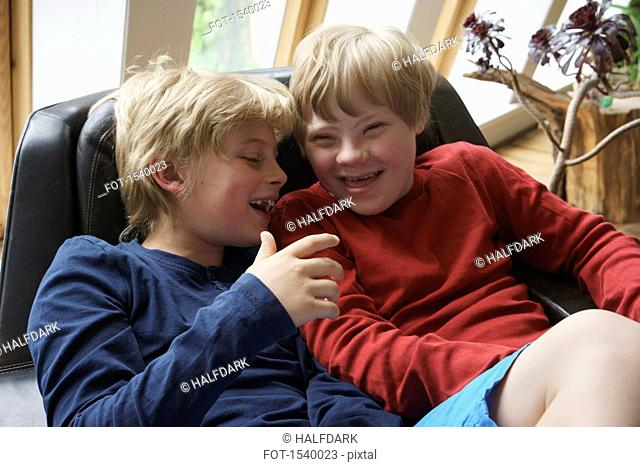 High angle view of happy brothers sitting on chair at home