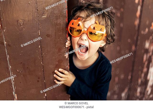 Portrait of little screaming girl wearing halloween glasses shaped like pumpkins