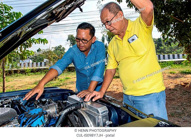 Friends inspecting engine of classic American muscle car