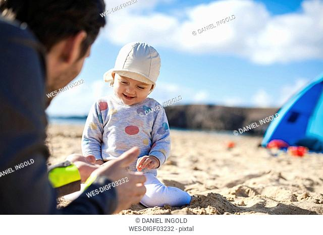 Spain, Lanzarote, happy baby girl playing with father on the beach