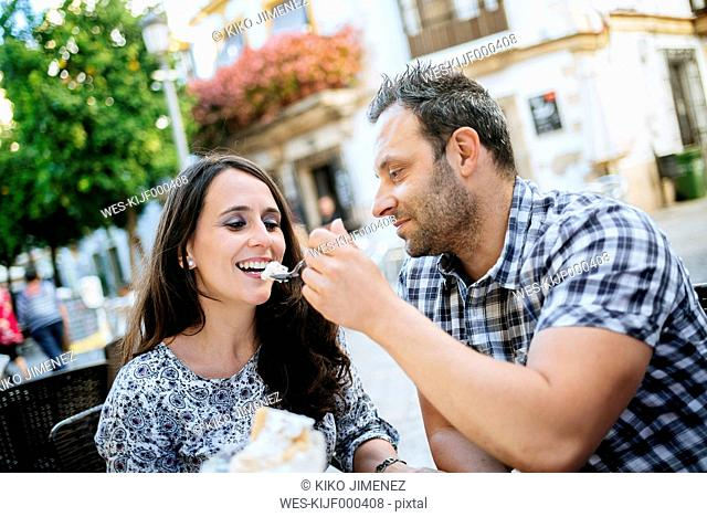 Couple eating ice cream in a street cafe
