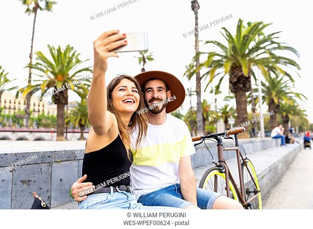 Spain, Barcelona, happy couple sitting on bench taking a selfie