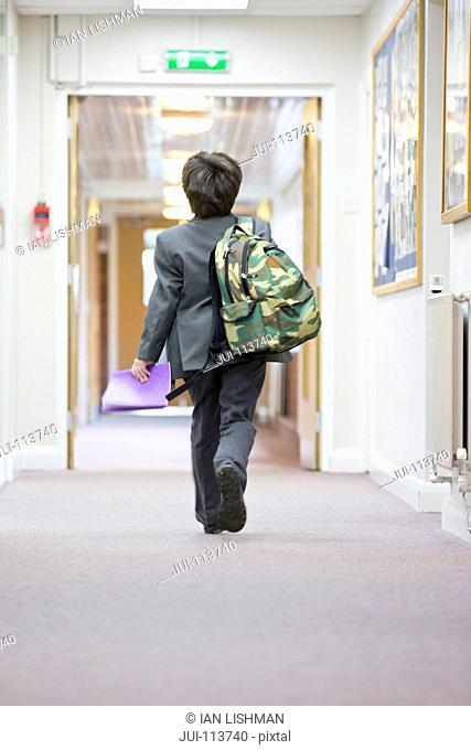 Middle school student with backpack walking in school corridor